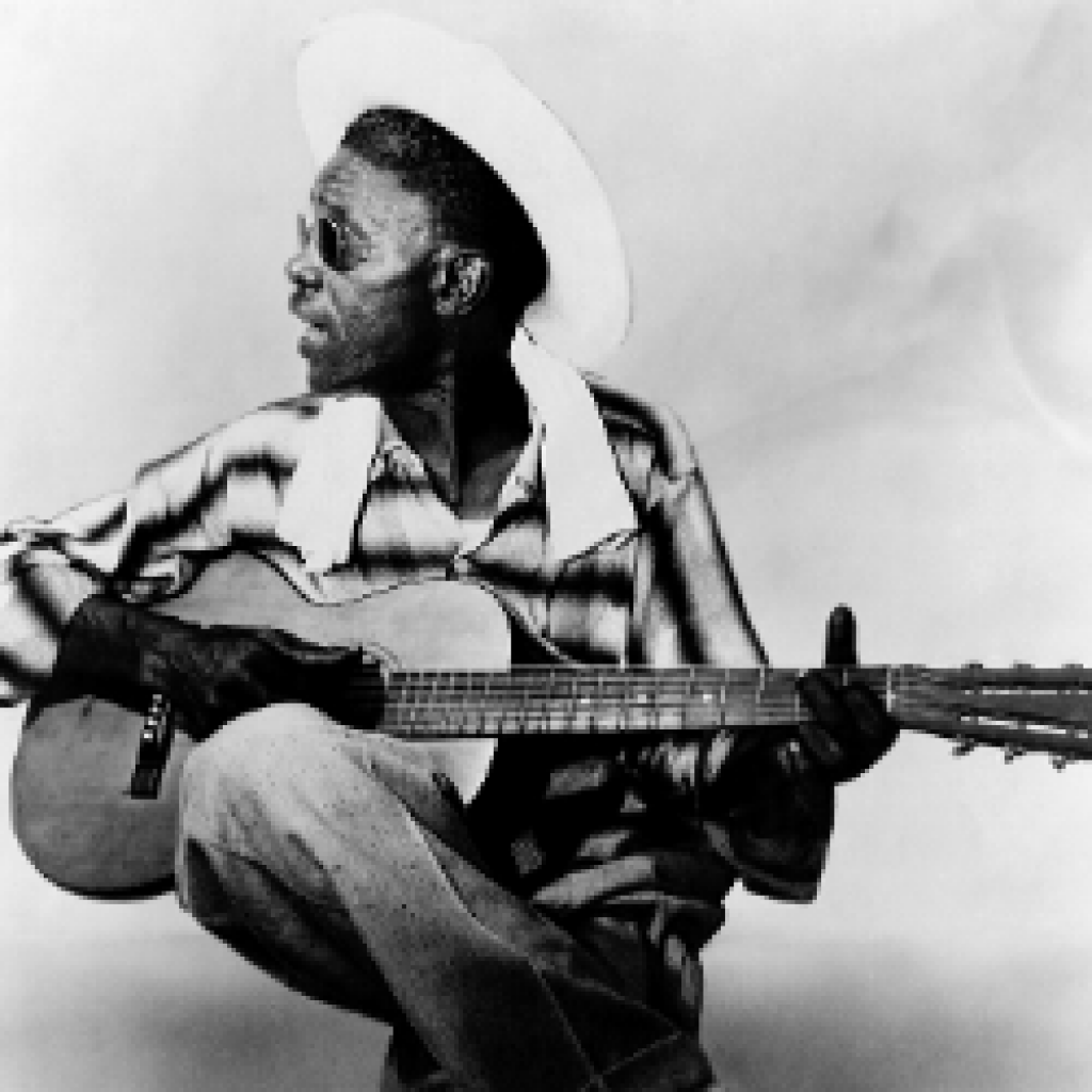 Lightnin' Hopkins, playing what appears to be a vintage Stella guitar, in casual clothes