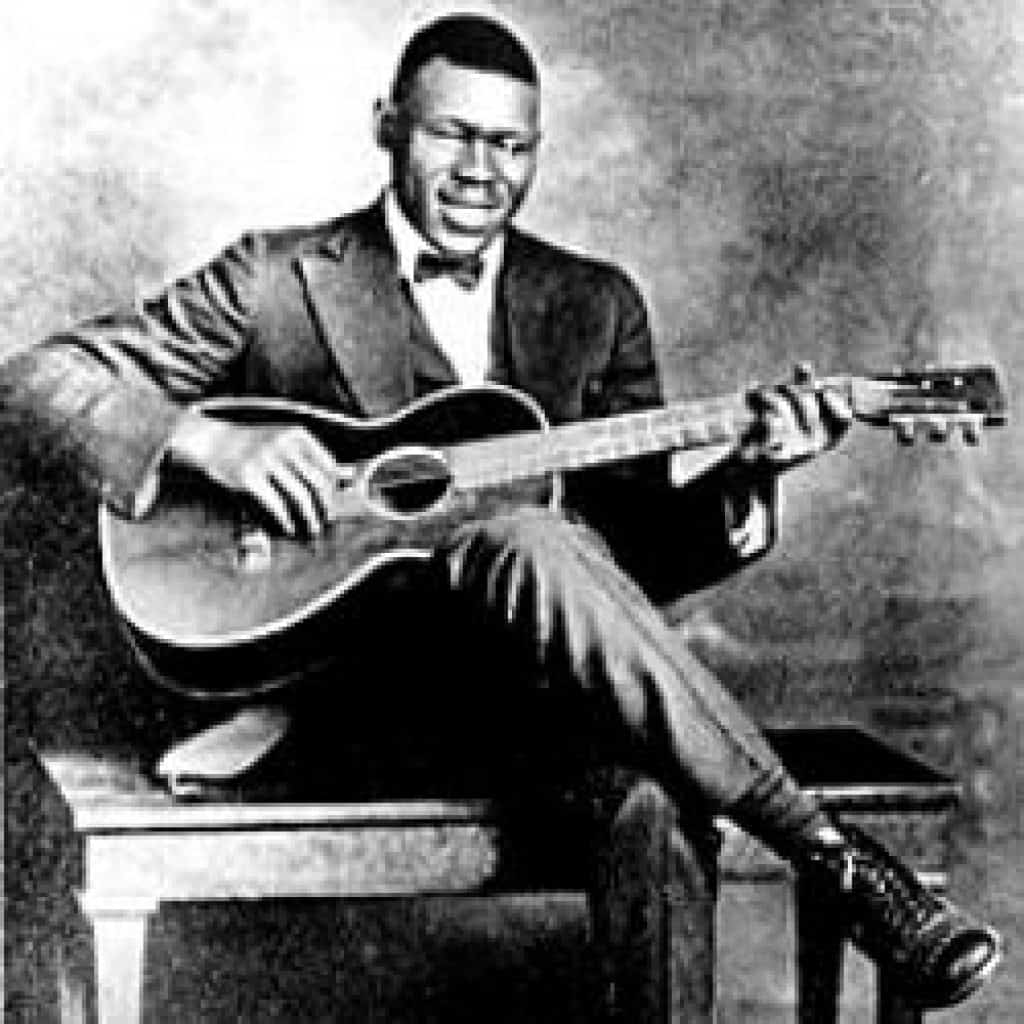 Piedmont/ragtime blues guitarist, Blind Blake, playing fingerstyle guitar for a promo photo